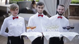 The waiters greet guests with alcoholic drinks. Champagne, red wine, white wine on trays.