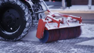 Tractor cleaning snow in the park. Snow plow outdoors cleaning street. snowplow removing fresh snow from city square