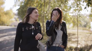 Two beautiful long hair women walking in blooming spring park and discussing latest gossip. Cute diverse girls talking while take a stroll in park in springtime.