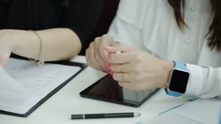Two business woman signing documents at the table. The process of signing a contract between two business women.