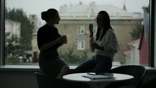 Two Business women near the window in the office drinking coffee at the end of the day and talk to hot gossip, commenting on the day.