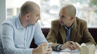 Two businessmen discuss the project over lunch. Two businessmen eating Chinese noodles and discussing a business project.