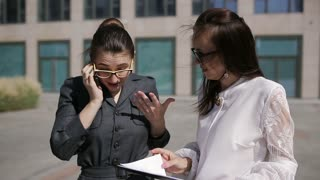 Two women near business center call up on the phone with the boss telling him important analytical information