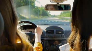 Two young girls travel in a car.