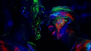 Ultraviolet people scream at each other. The conflict between a man and a woman.