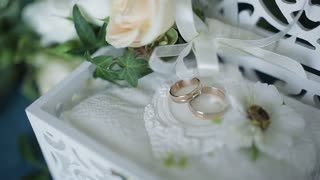 Wedding concept. Wedding rings in a wooden box handmade, surrounded by flowers on a turquoise background.