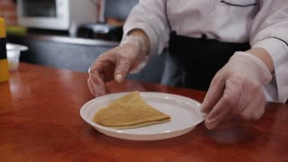 Woman cook in restaurant watering pancakes with condensed milk