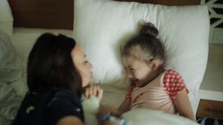 Woman waking young girl in bed smiling, Mother coming to the sleeping child