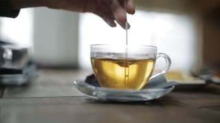Woman's hand stir the sugar in a Cup of tea in a cafe at the airport