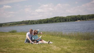 young couple in love on a date on the grass by the river. A guy and a girl on a walk with a dog.