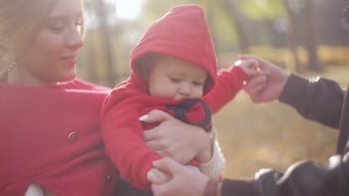 young family playing with baby in autumn park. Happy motherhood and childhood. Parents enjoy their child