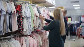 Young happy pregnant woman choosing newborn clothes at the baby shop store stock footage video