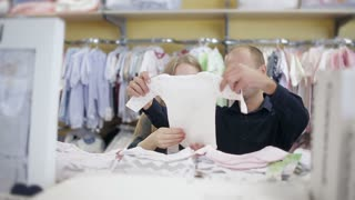 Young husband with his pregnant wife buying clothes for newborn in baby and maternity shop