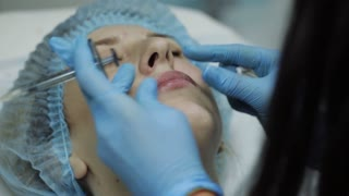 Young woman on lip Augmentation in a clinic. Anesthetic injection Silicone implant lips thickening injection