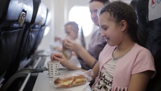 Young woman sits in chair near illuminator of airplane and eats meal for passenger