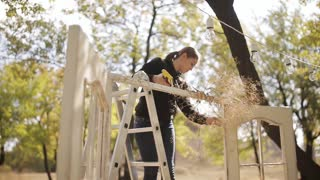 wedding decorator decorates wedding arch in the form of doors in nature in a rustic style