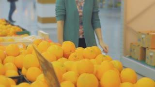 Woman choosing orange at fruit vegetable supermarket