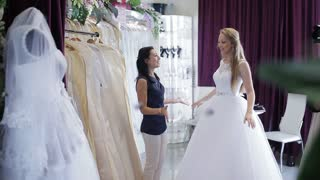 Woman choosing wedding dress in shop