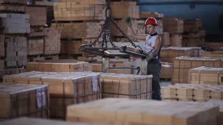 woman Factory worker in helmet transporting packing firebricks with workshop rail mounted gantry crane
