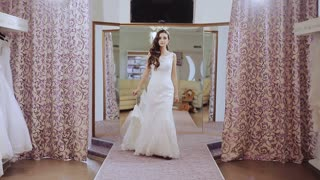 woman in a wedding dress walks down the catwalk and spinning in a wedding salon