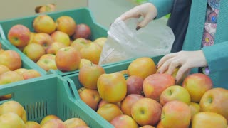 Woman in the supermarket coming up to the fruit counter. She choosing and putting apples in plastic bag