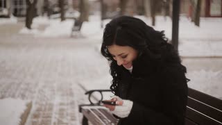 woman in winter park talking mobile phone, sms, sitting on the bench