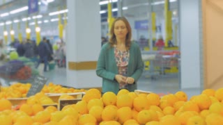 Woman selecting fresh oranges in grocery store produce department and smelling it. Young pretty girl is choosing fruits in supermarket