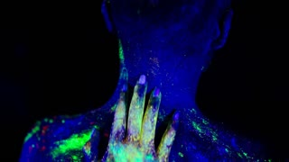 Women's hand passionately embraces the head of a man in the ultraviolet light.