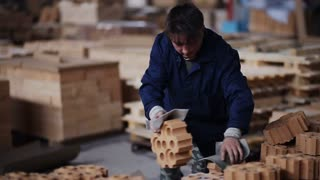 Work on the factory floor packs products. factory workers adds refractory bricks for further packaging.