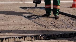 Worker operating asphalt repairing works