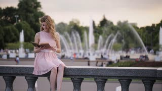 young attractive girl in a summer park fountain reads a book with interest