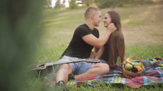 Young beautiful couple dressed casual having picnic in park, eating grape and drinking wine.
