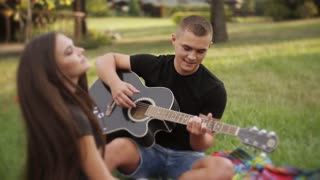 Young beautiful couple smiling, resting in park. Man playing guitar. A romantic date on nature.