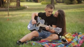 Young beautiful couple smiling, resting in park. Man playing guitar.