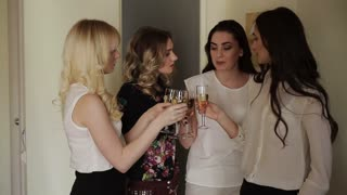 young beautiful girls congratulate her friend a happy birthday with glasses of champagne