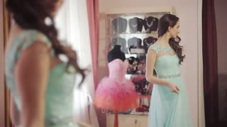 young beautiful woman chooses a dress in the salon for graduation ball