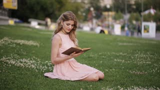 young blonde girl in the park reading a book on the grass