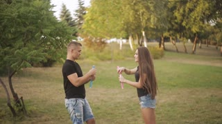Young couple funny plaing with Soap bubbles