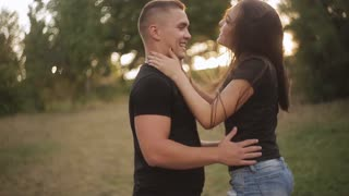 Young couple having fun in the park at the sunset. Romantic date