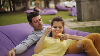 young couple having fun in the park with soap bubbles
