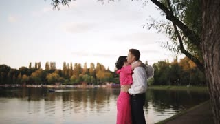 Young couple in love kissing in the park by the river