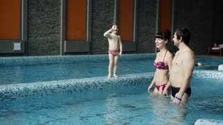 Young family in the pool teaching his son to swim. A boy jumps into the water.