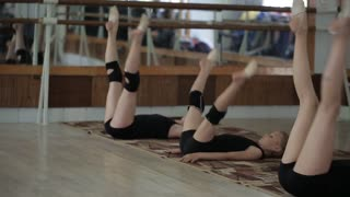 Young girls are trained in the gym. The exercises in rhythmic gymnastics.
