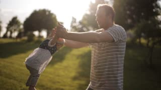 young happy dad turns his little daughter in a park at sunset
