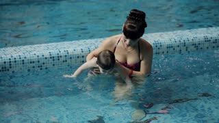 Young parents in the pool teaching his son to swim under water