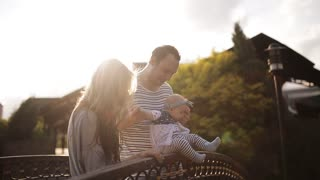 Young parents with a baby on the bridge in the park at sunset