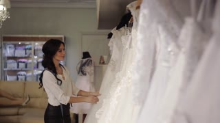 young salesman bridal salon chooses dress for the bride