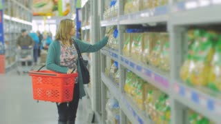 Young woman chooses food in the supermarket, Mother chooses food for their child in the market, girl stands near the supermarket shelf and selects the products