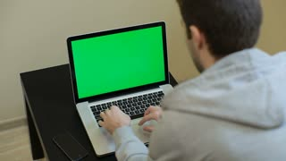 A man types on a laptop. Young Handsome Man Sits and Works on Green Screen Laptop