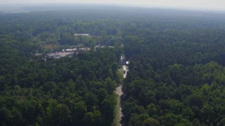 Aerial view of the road through green forest. Meat factory